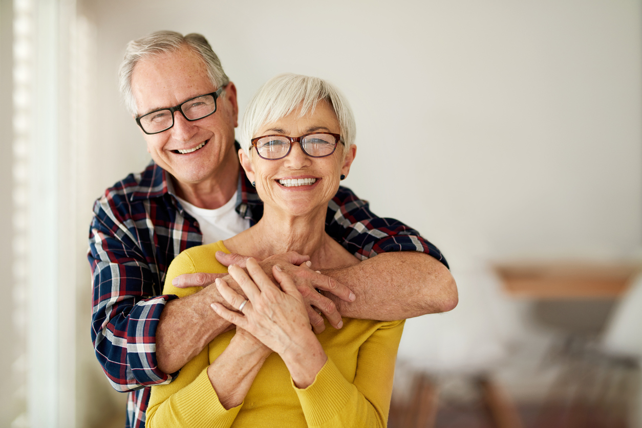 Cropped portrait of a senior man affectionately embracing his wife at home